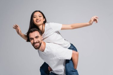 Young man in white t-shirt piggybacking excited asian girlfriend imitating flying isolated on grey stock vector