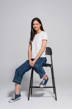 Brunette asian woman in jeans, gumshoes and white t-shirt sitting on chair and looking at camera on grey stock vector