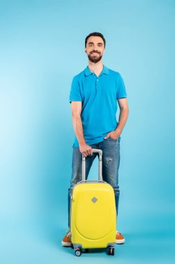 Young tourist in polo t-shirt and jeans holding hand in pocket while standing with yellow suitcase on blue stock vector