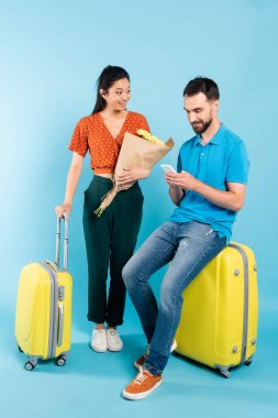 Asian woman in red blouse holding bouquet near boyfriend sitting on suitcase with smartphone on blue stock vector
