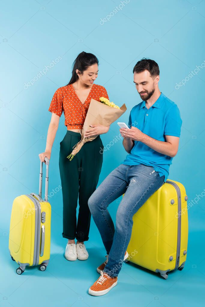 Asian woman in red blouse looking at bouquet near boyfriend using smartphone while sitting on suitcase on blue stock vector