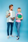 zrzka student drží knihu a kávu jít při pohledu na blondýny mladá žena s notebooky na modré