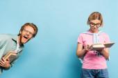 vzrušený a zrzka muž dívá na kameru, zatímco blondýny žena čtení knihy na modré
