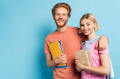 bearded man holding notebooks and hugging blonde student with books on blue