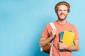 rothaarige Studentin hält Notizbücher in der Hand und berührt Rucksack auf blau