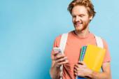 zrzka student držení notebooky a pomocí smartphone na modré