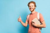 szakállas diák gazdaság könyv és mutatja hüvelykujját fel a kék