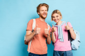 mladí studenti s batohy ukazující palce nahoru na modré
