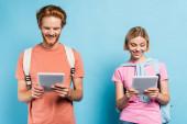 mladí studenti se dívají na digitální tablety na modré