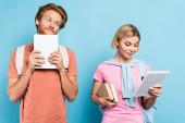 zrzka muž při pohledu na blondýny student drží knihy a digitální tablet na modré