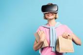 junge blonde Studentin im Virtual-Reality-Headset mit Büchern und Papiertüte auf blauem Hintergrund