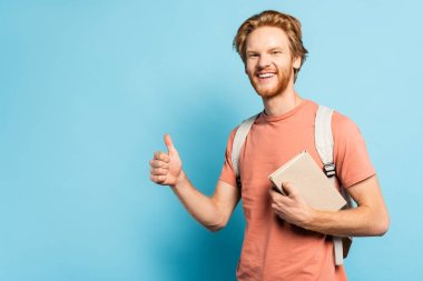 Bearded student holding book and showing thumb up on blue stock vector