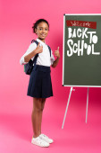 Photo african american schoolgirl near chalkboard with welcome back to school lettering showing thumbs up on pink