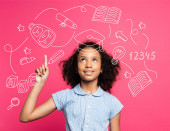 curly african american kid pointing with finger and looking up near illustration on pink