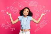 curly african american kid showing shrug gesture near illustration on pink