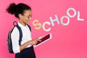 afrikanisch-amerikanische Schülerin in Brille mit Rucksack mit digitalem Tablet in der Nähe der Schule Schriftzug auf rosa