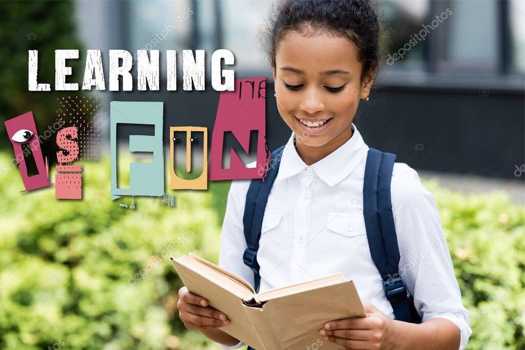 African american schoolgirl reading book near learning is fun lettering outdoors stock vector