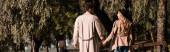 horizontální obraz páru v pláštích zákopů držících se za ruce a procházejících se v podzimním parku