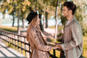 side view of man and woman in trench coats holding hands and looking at each other while standing in autumnal park