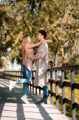 side view of excited couple hugging while standing on wooden bridge