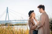 žena v klobouku a muž objímající a dívající se na sebe venku