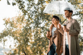 couple in trench coats standing under umbrella and holding paper cups with coffee to go