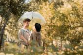 szelektív fókusz nő kalapban és férfi ballonkabátban álló ernyő alatt őszi parkban