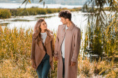 pleased woman and man in trench coats holding hands near lake in autumnal park