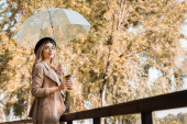 woman in hat holding umbrella and disposable cup with coffee to go in autumnal park