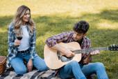 žena drží sklenici červeného vína a dívá se na přítele hraje na akustickou kytaru