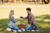 oldalnézetben férfi és nő ül kockás takaró és koccintó pohár vörösbor