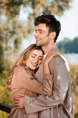 Woman with closed eyes hugging man in trench coat outside stock vector