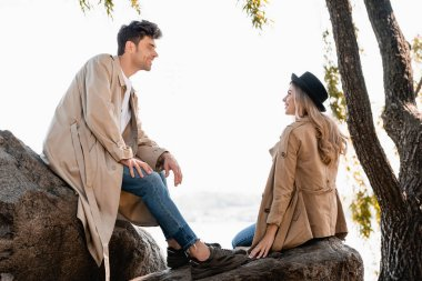 Blonde woman in hat and man in trench coat sitting on stones and looking at each other stock vector