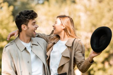 excited woman holding hat and looking at boyfriend in autumnal park