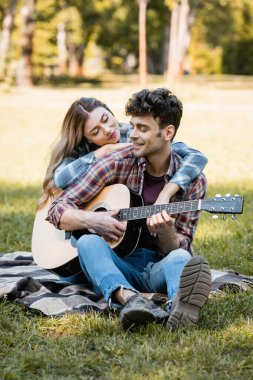woman sitting on plaid blanket and touching boyfriend playing acoustic guitar