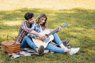 woman sitting on plaid blanket and playing acoustic guitar with boyfriend