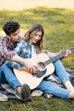 woman sitting on blanket and playing acoustic guitar with boyfriend