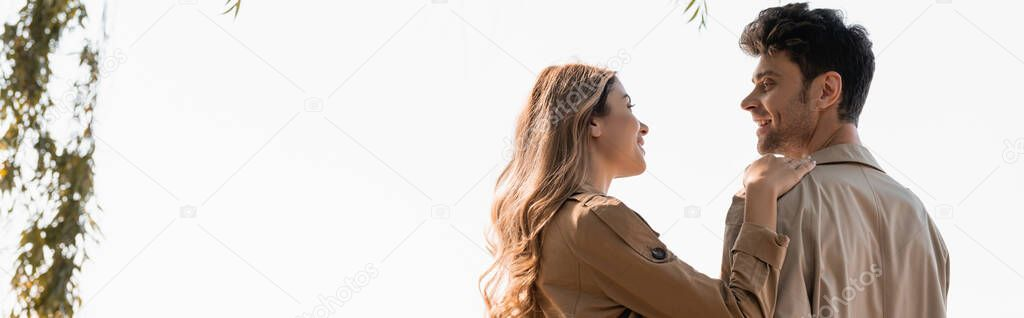 Blonde woman touching and looking at joyful boyfriend, panoramic crop stock vector