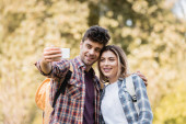 joyful man and woman taking selfie in autumnal park