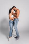 muskulöser Mann steht und berührt verführerische Frau im BH auf grau