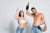 Hemdloser Mann mit Eiskübel und Champagnerflasche neben sexy Frau in BH mit Brille auf grau