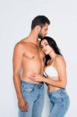 Fotografie brünette Frau im BH umarmt muskulösen und bärtigen Mann isoliert auf weiß