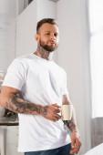 seriózní potetovaný muž v bílém tričku při pohledu do kamery, zatímco drží šálek čaje