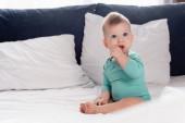 selektivní zaměření kojeneckého chlapce v batole sedí v posteli s rukou v ústech
