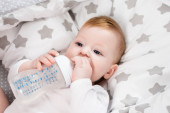 infant boy holding baby bottle while lying on bedding with stars print