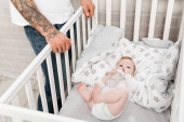 tattooed man standing near infant son lying in cot with baby bottle