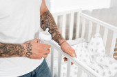 cropped view of tattooed man holding baby bottle while standing near cot