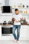 mladý muž v bílém tričku a džínách holing miska se snídaní, zatímco stojí v kuchyni