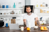 bearded, tattooed blogger in white t-shirt looking at camera near breakfast and laptop in kitchen
