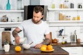 mladý tetovaný muž v bílém tričku nalévá čerstvé mléko do misky při snídani v kuchyni